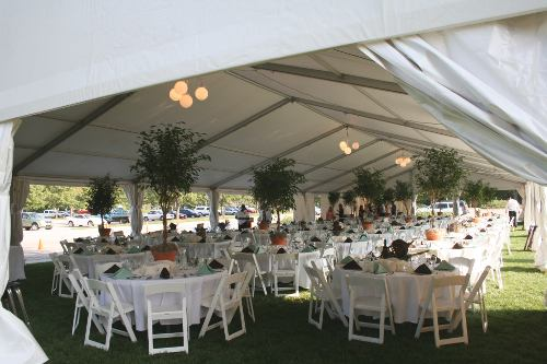 Image of decorated tent set in Lincoln with white tables and greenery