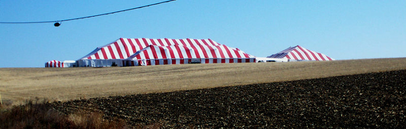 Image of large red and white striped tent set in coutryside.