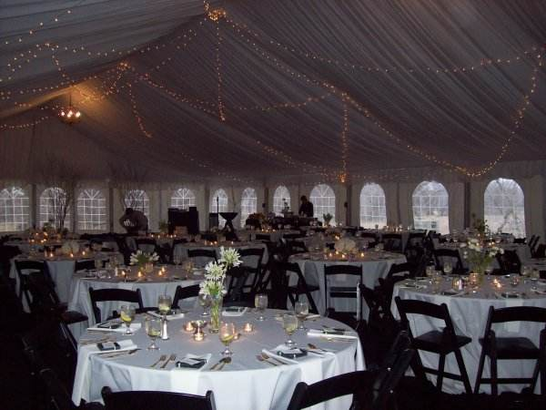 Interior of a wedding tent set for a wedding reception. It shows the elegant decorations