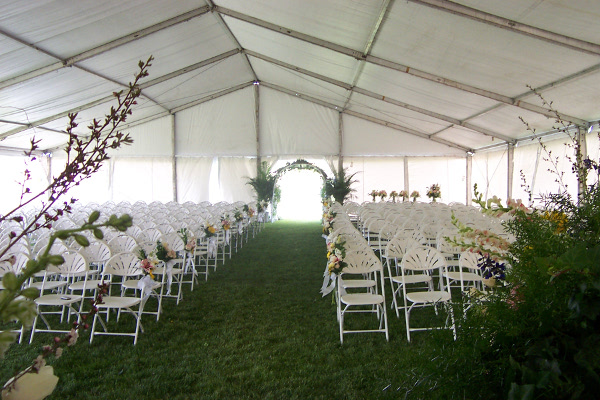Image of a clear span tent set for an outdoor wedding