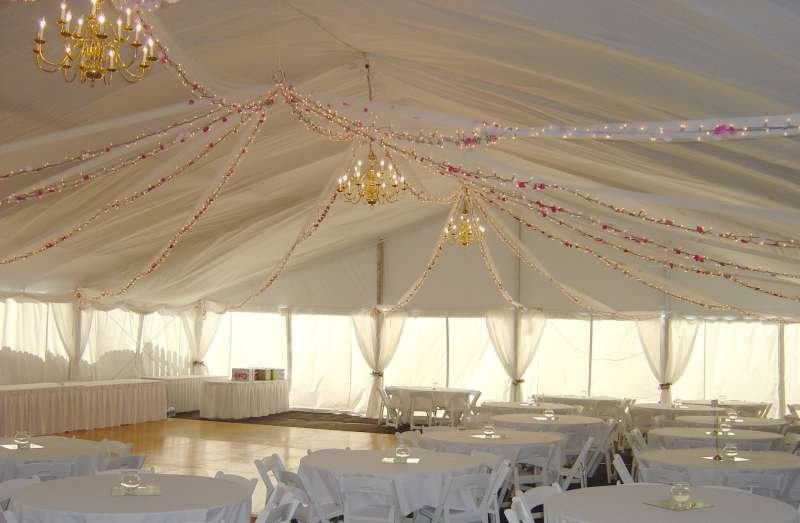 Clear span structure for wedding with white liner and brass chandeliers
