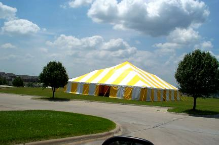 Big Yellow & White Commercial Pole Tent set in a pretty green space