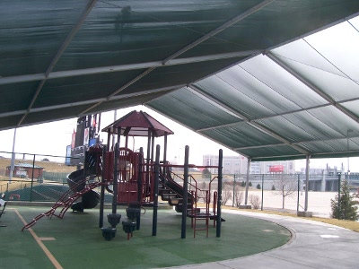 Image of inside shade structure over large playground slide.