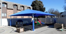 Image of a shade structure over a playground area.