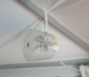Image of small mounted fan inside of tent setup for wedding reception.