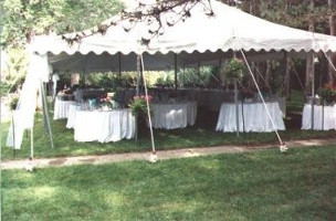 Image of an elegant but simply decorated tent set up for a large reception